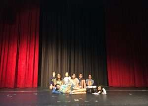 Kids on stage with red curtain